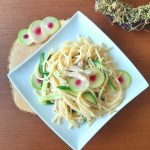 Green pasta with shredded chicken decorated with watermelon radish top view