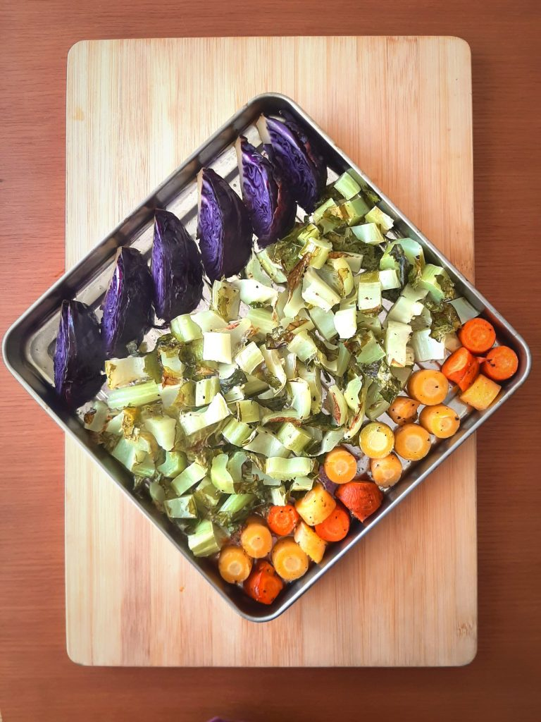 Top view of roasted cauliflower greens with carrots and purple cabbage