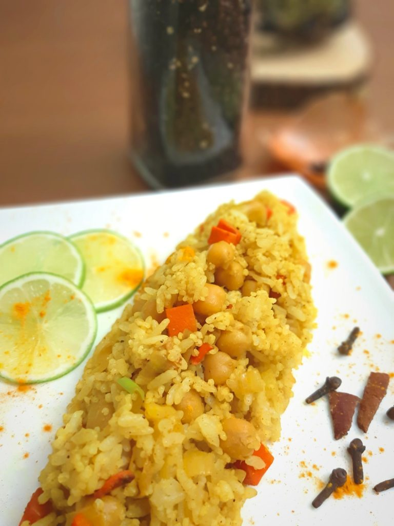 Yello Rice on a plate with pepper, lime and spices