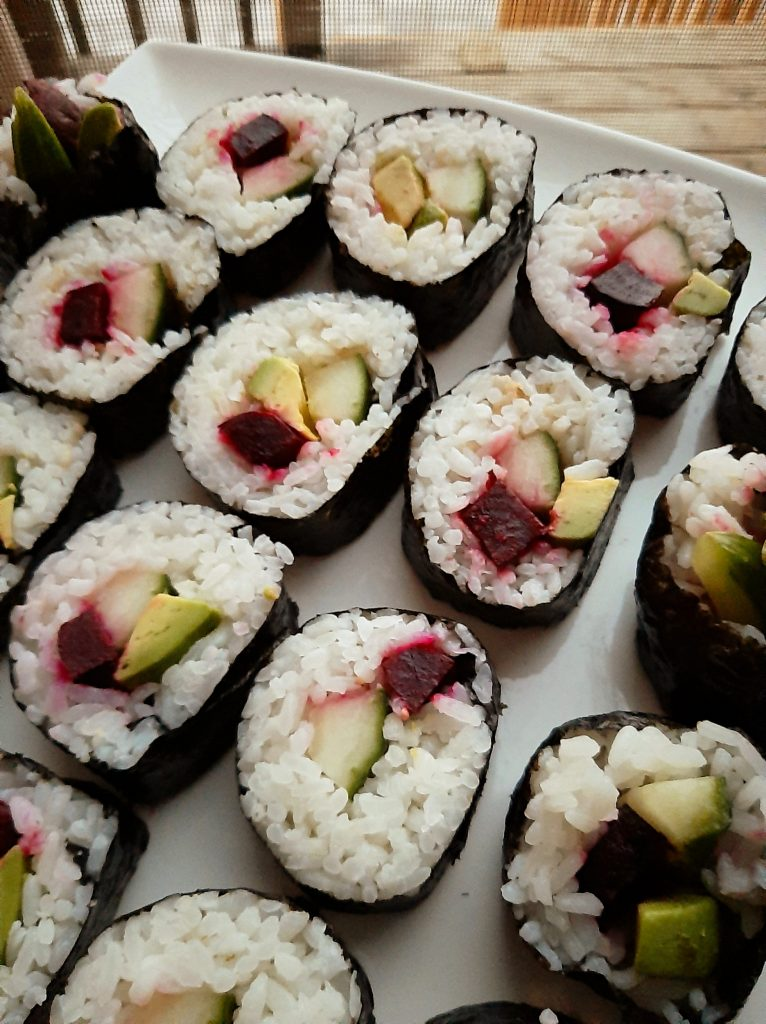 Vegan sushi roll with cooked beets, avocado and cucumber