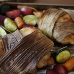 Corn husk-wrapped chicken and roasted veggies at an low angle