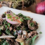 Chicken livers and onions with Swiss chard at an angle with green onion bunch and red onion in the background