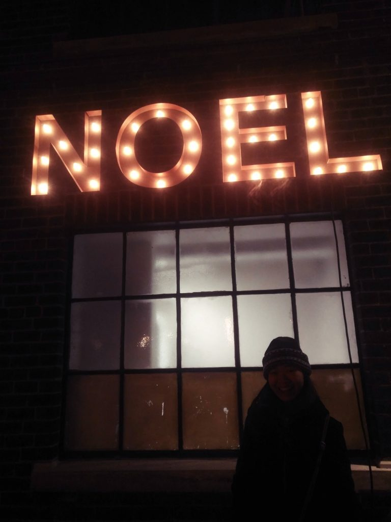 Noel light bulb sign on the wall with Brenda standing in front of it