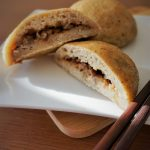 Cross section of gluten free baked bbq pork buns on a plate with chopsticks