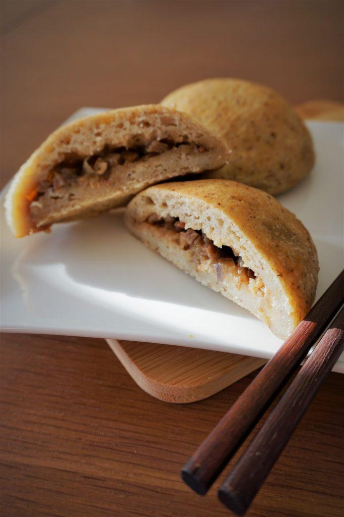 Cross section of gluten free bbq pork bun on a plate with chopsticks